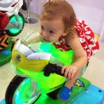 Olivia racing on toy bike. Where's Your Helmet Girl?